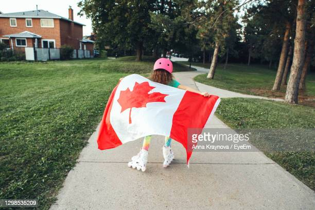 girl wrapped in large canadian flag riding on roller skates in park. canada day celebration - canada day stock pictures, royalty-free photos & images
