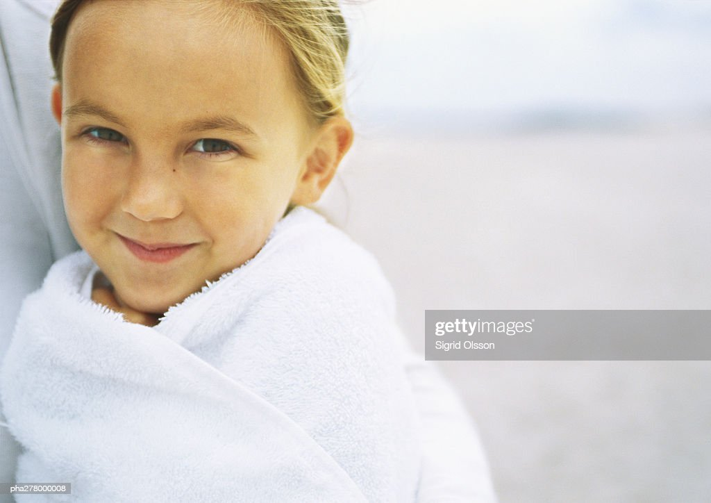 Girl wrapped in towel on beach, portrait : Stockfoto