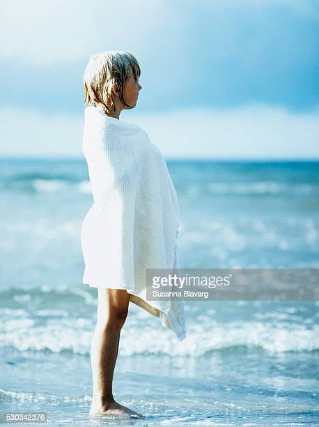 girl wrapped in towel standing in sea waves - filme de arquivo - fotografias e filmes do acervo