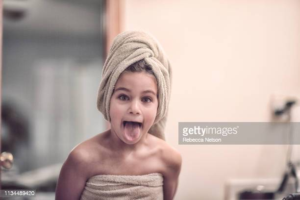 Girl wrapped in towel wearing towel on head looking at camera sticking out tongue