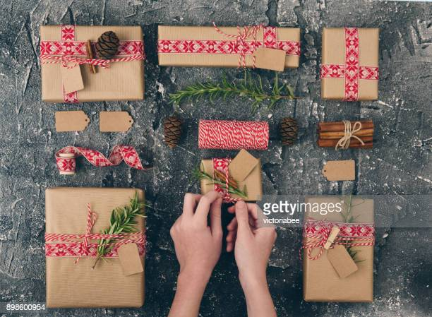 girl wrapping christmas gifts and arrangement of gifts - brown paper stock pictures, royalty-free photos & images