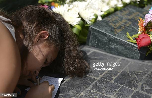 Girl writes a message by the tomb of Colombian drug lord Pablo Escobar at Montesacro cemetery in Medellin, Antioquia department, Colombia on December...