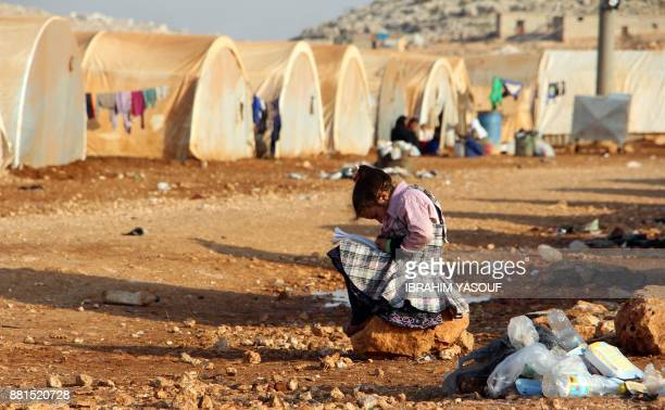 A girl writes in a notebook as she sits outside a tent at the Furat camp for the displaced from Deir Ezzor north of the town of Kafr Dariyan in the...