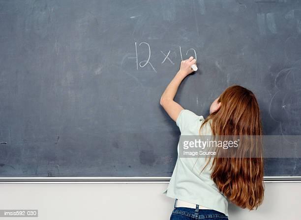 Mädchen schreiben den Betrag auf Tafel