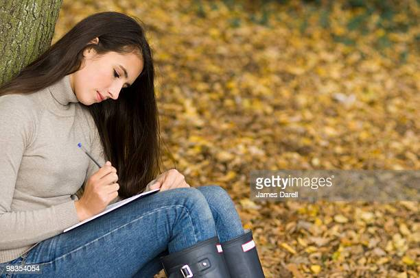 girl writing against a tree