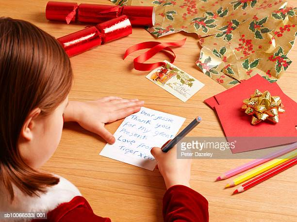 girl (6-7) writing christmas cards, over the shoulder view - answering stock pictures, royalty-free photos & images