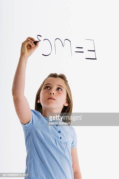 Girl (8-9) writing formula, on white background