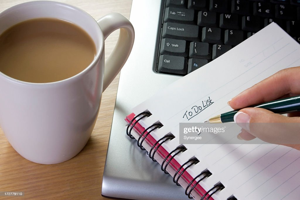 A girl writing her to do list in her notebook : Stock Photo