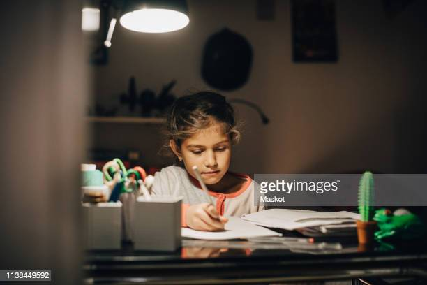 girl writing homework on desk while sitting against wall at home - angle poise lamp stock pictures, royalty-free photos & images