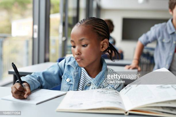 girl writing in book in classroom - コーンロウ ストックフォトと画像