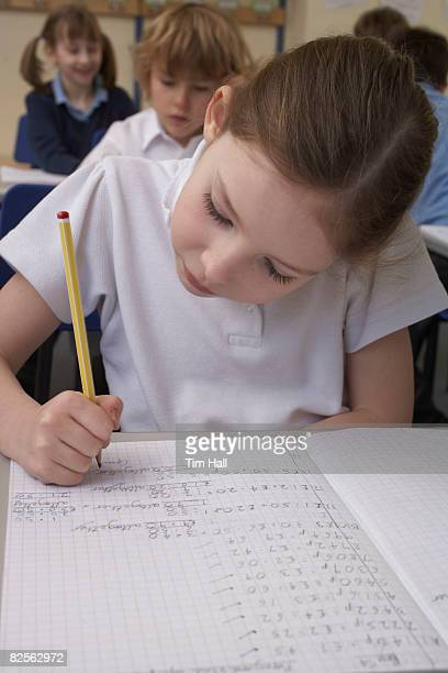 Girl writing in classroom