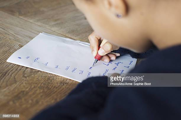 Girl writing in cursive on paper, cropped