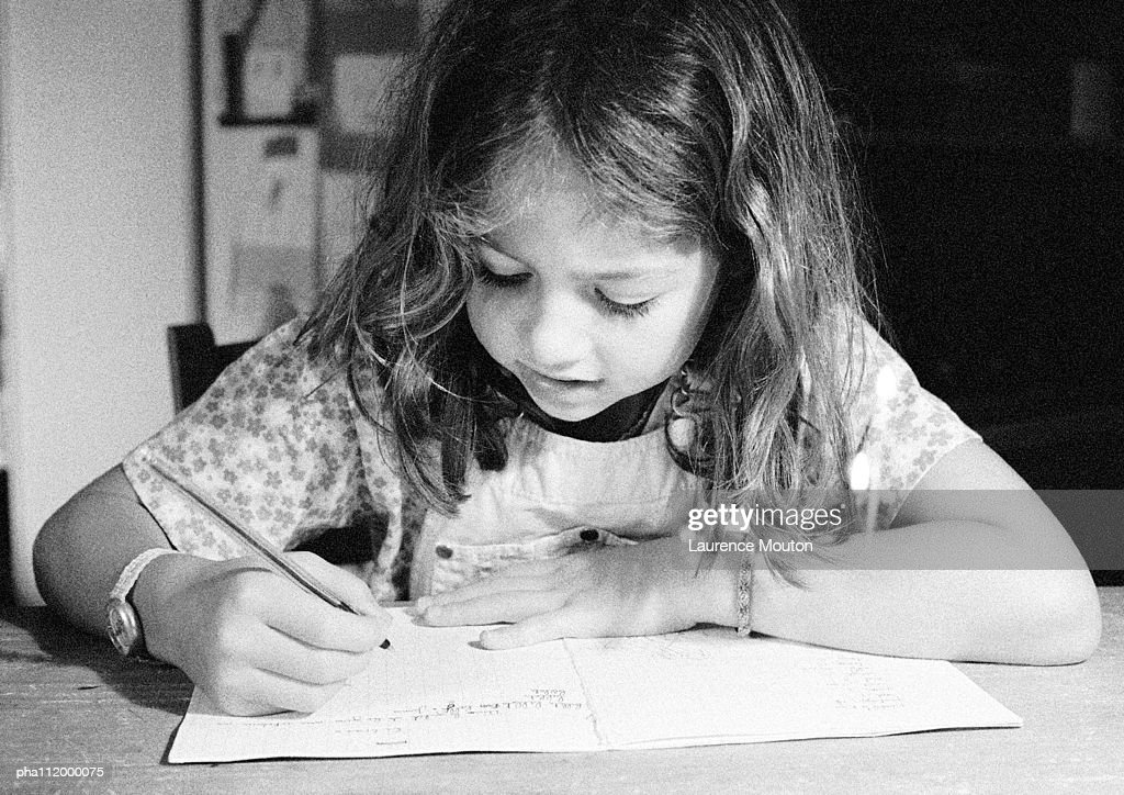 Girl writing in notebook, close-up, b&w : Stockfoto