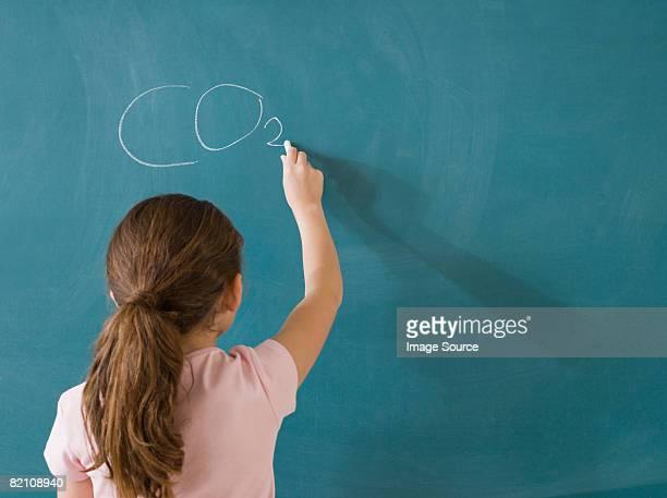 Girl writing on a blackboard