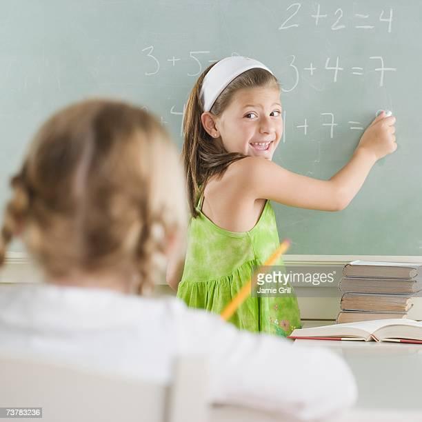 Girl writing on blackboard and smiling