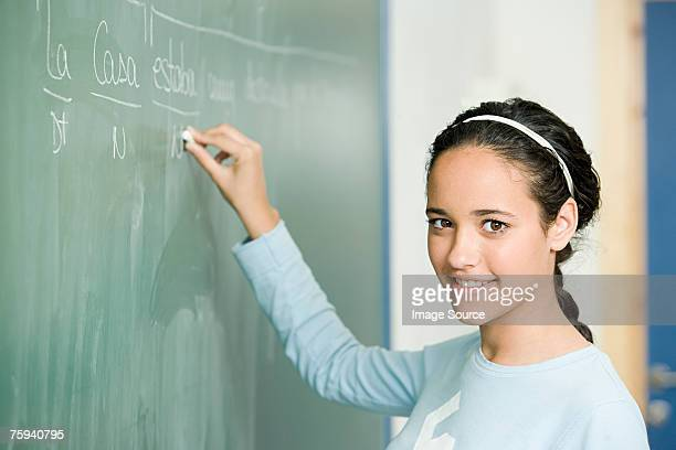 girl writing on blackboard - spanish culture stock photos and pictures
