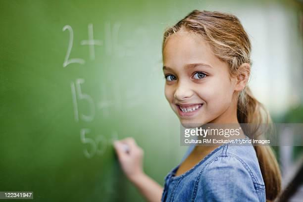 Girl writing on chalkboard in classroom