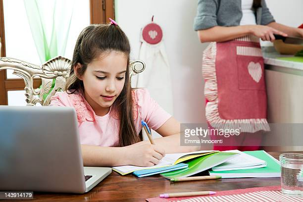 girl writing on exercise book on kitchen table