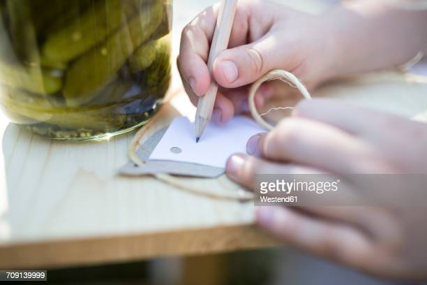 Girl writing on label next to jar with preserved gherkins