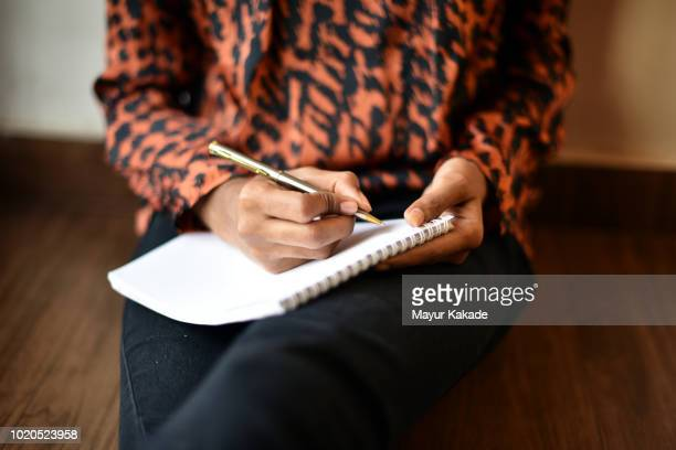 girl writing on notepad - parte do corpo humano imagens e fotografias de stock