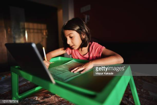 girl writing on paper using digital tablet - learning disability stock pictures, royalty-free photos & images