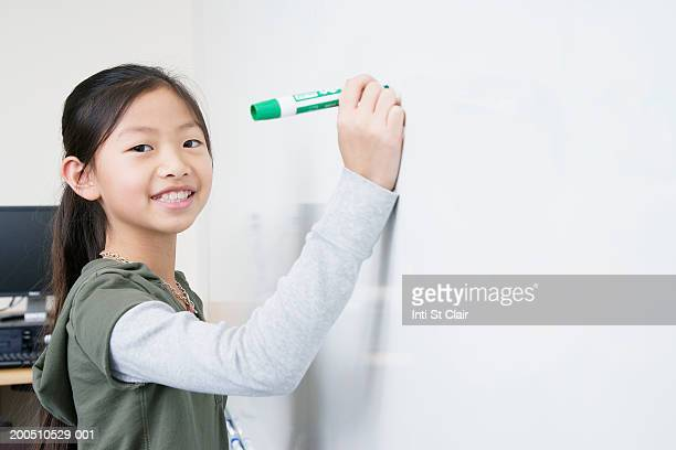 Girl (8-10) writing on whiteboard, portrait, side view