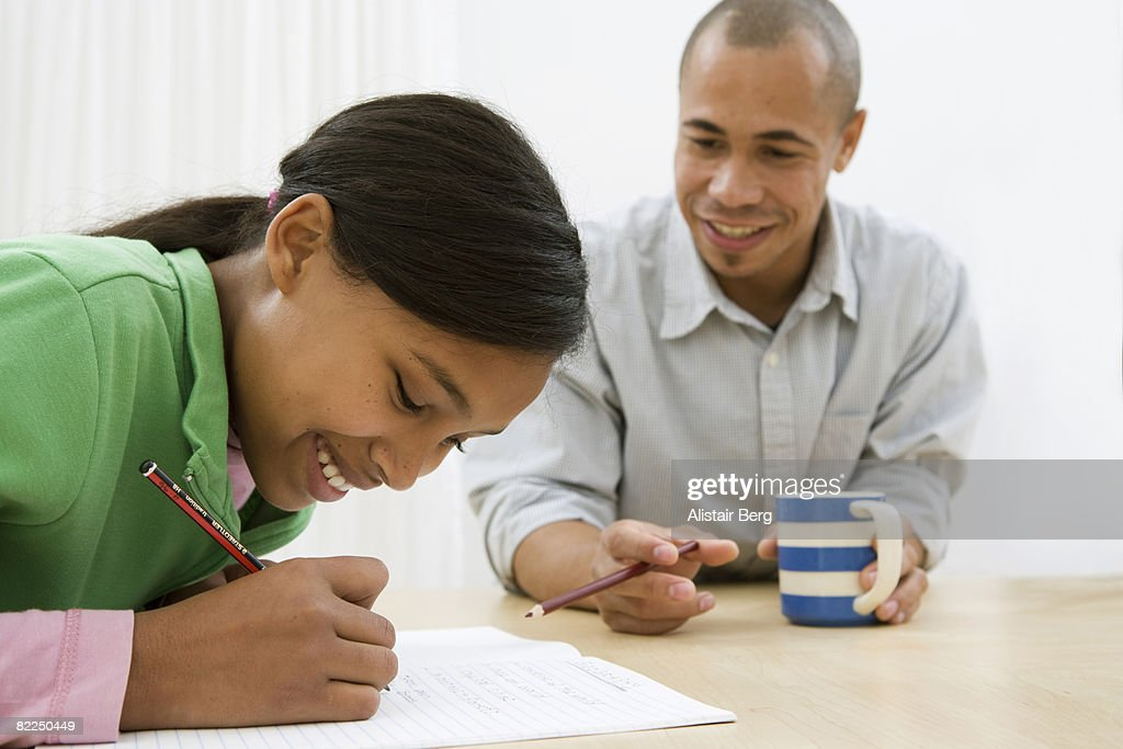 Girl writing with dad in background : Stock Photo