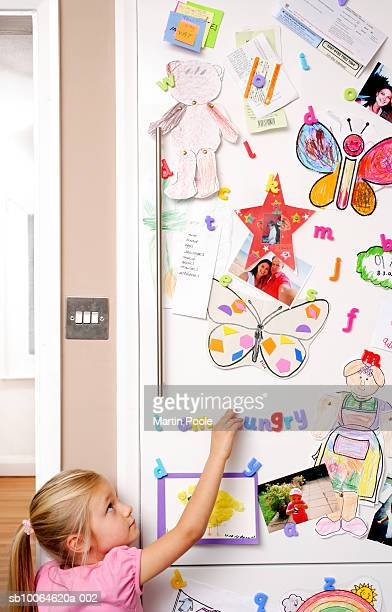 Girl (4-5) writing word in magnets on refrigerator