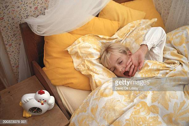 Girl (6-7) yawning in bed, eyes closed, elevated view