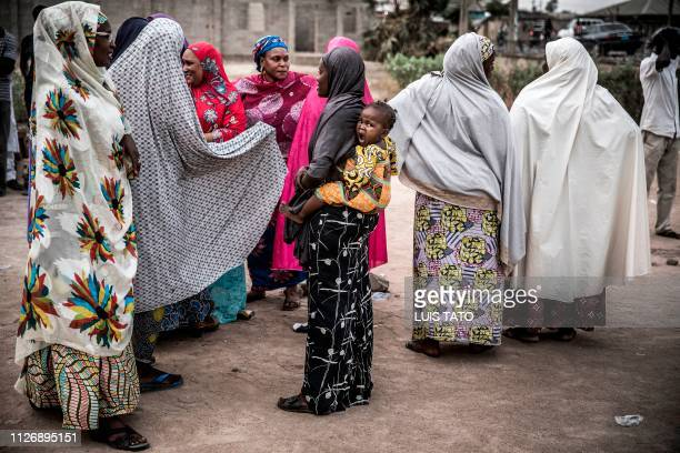 A girl yawns when carried by her mother when some women gather together during the closing of their polling unit at Shagari Health Unit polling...