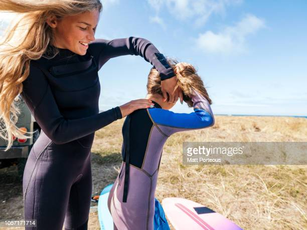 Girl zipping up wetsuit