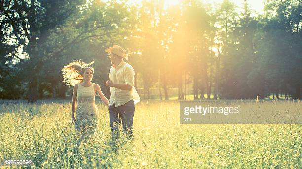 Girlfriend and boyfriend holding hands and running across a meadow