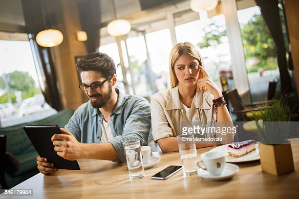 Girlfriend annoyed with boyfriend using digital tablet on date.