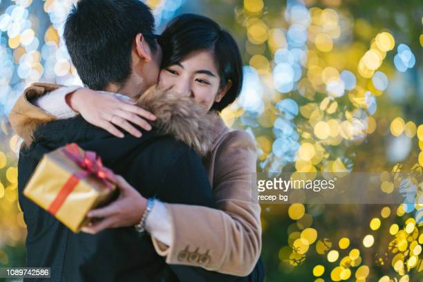 girlfriend happily hugging her boyfriend while holding gift box - anniversary stock pictures, royalty-free photos & images