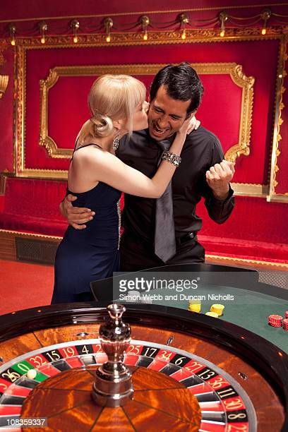 Girlfriend kissing winning boyfriend at roulette table