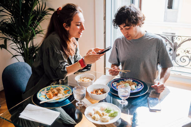 Girlfriend taking photo of food through mobile phone while having lunch with boyfriend at home
