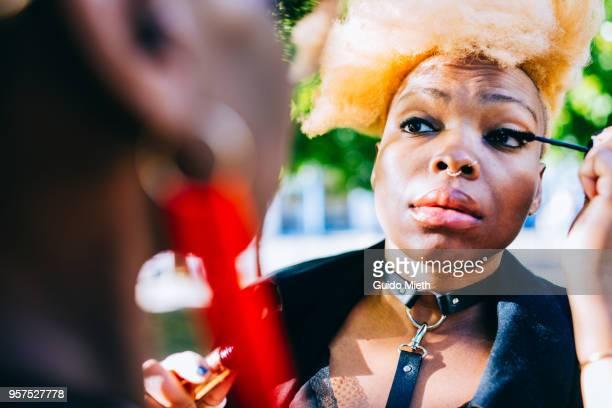 Girlfriends applying makeup outdoor.