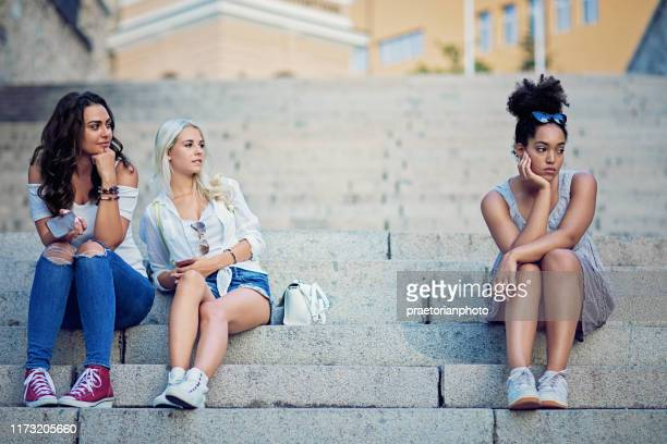 girlfriends are bullying a girl at the city stairs - cruel stock pictures, royalty-free photos & images