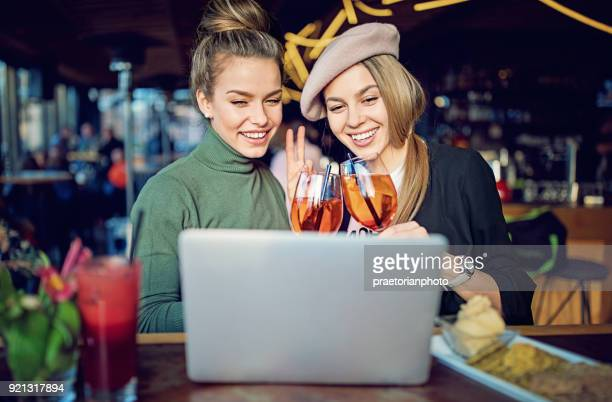 girlfriends are cheering with cocktails in the bar and making video call - very young webcam girls stock photos and pictures