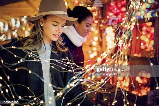 namoradas estão escolhendo presentes e decoração no mercado de natal - mercado natalino - fotografias e filmes do acervo