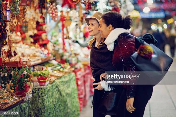 girlfriends are choosing gifts at the christmas market - souvenir stock pictures, royalty-free photos & images