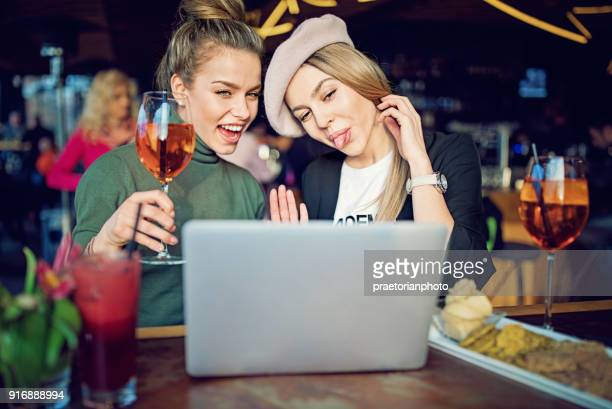 girlfriends are drinking cocktails in the bar and making video call - little girls webcam stock photos and pictures