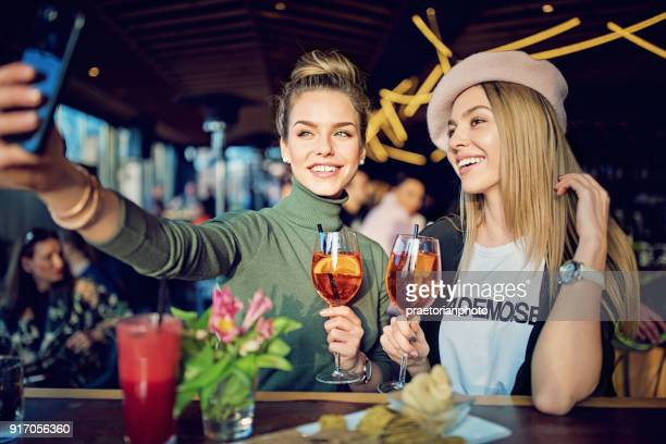 girlfriends are drinking cocktails in the bar and taking selfie/making video call - girlfriend stock pictures, royalty-free photos & images