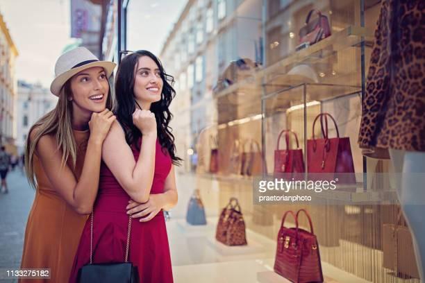 copines regardent dans la fenêtre de magasin de sac - petite amie photos et images de collection