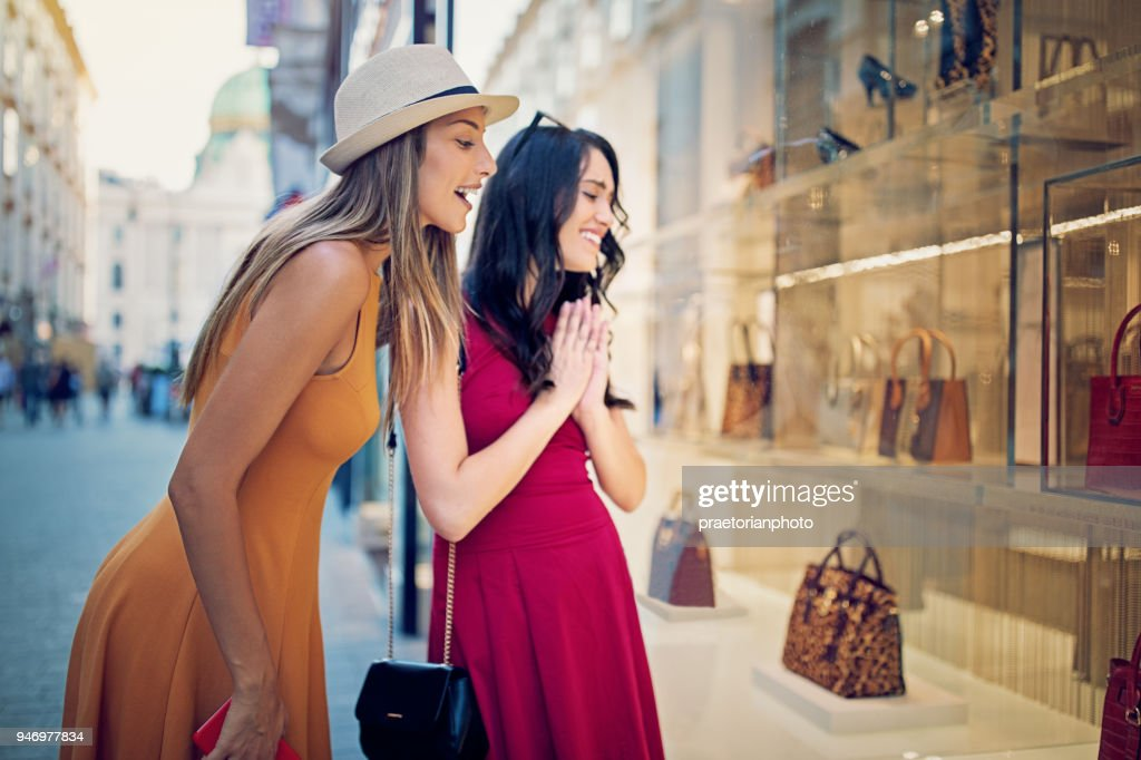 Girlfriends are looking in the bag store window : Stock Photo