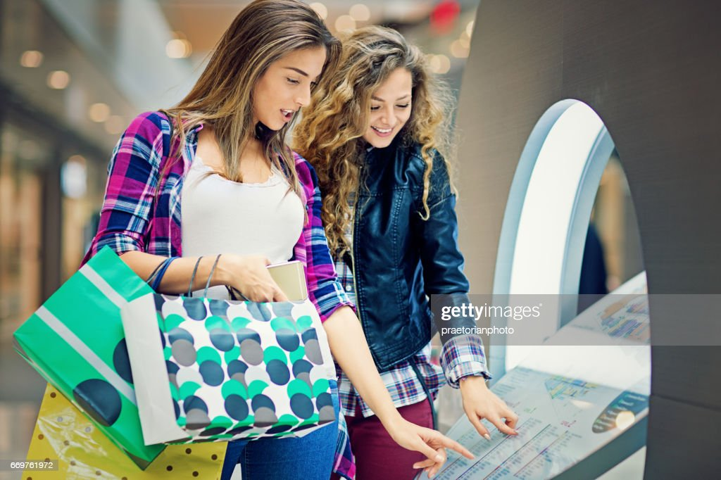 Girlfriends are looking store directory in the Mall : Stock Photo