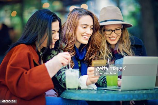 Girlfriends are shopping online in the cafeteria