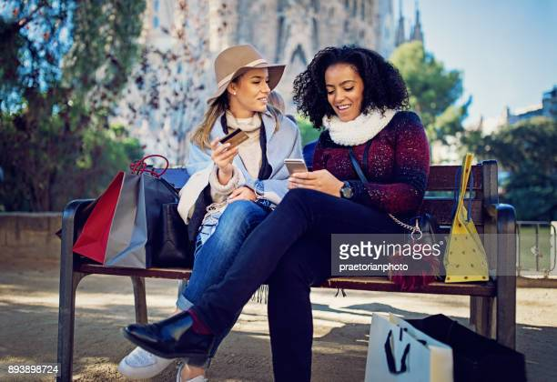 Girlfriends are shopping online on the bench at the front of La Sagrada Familia cathedral