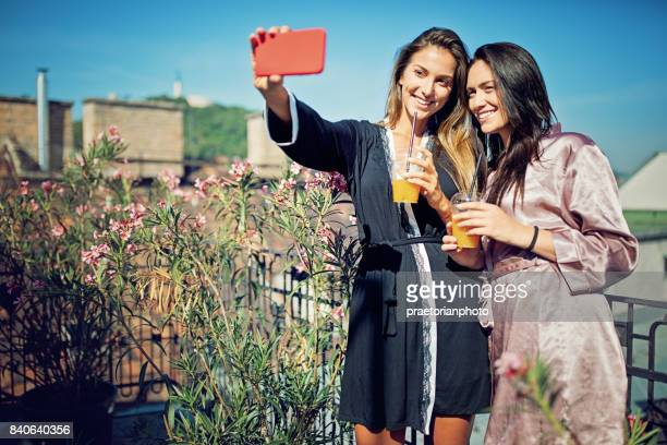 Girlfriends are taking selfie/making video call on the roof terrace in the morning