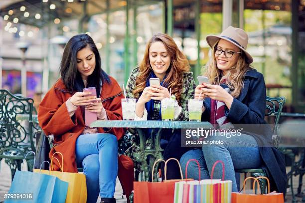 Freundinnen sind SMS in einem Café nach dem Einkauf